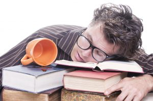 Exhausted young male Caucasian student with glasses asleep on pile of books next to spilled cup of coffee